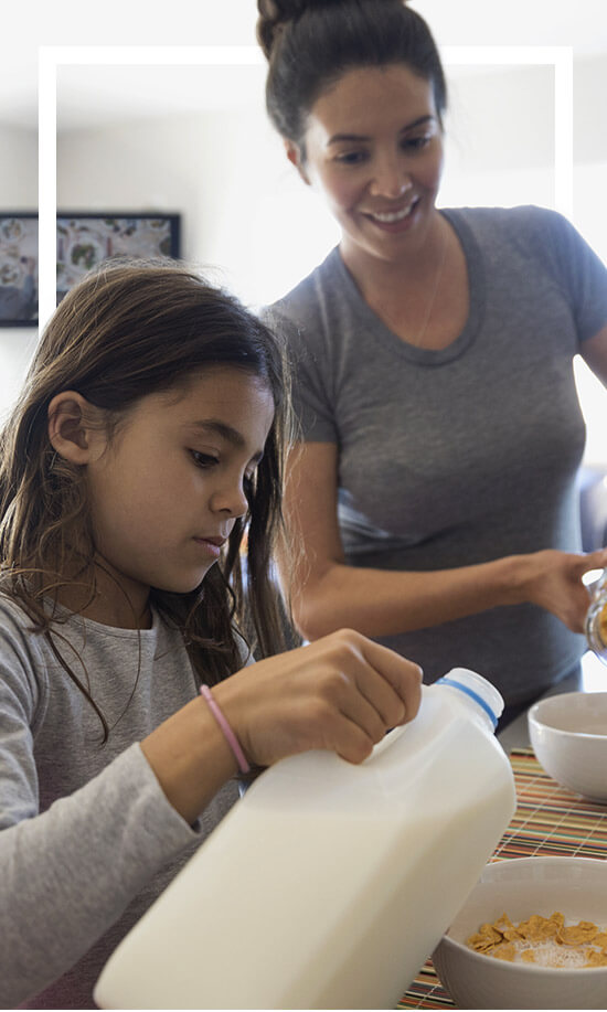 Mother and daughter making cereal