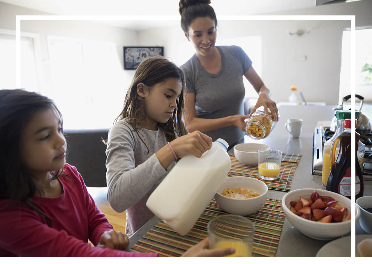 Mother and children making cereal